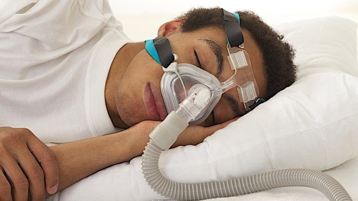 man sleeping with cpap machine on