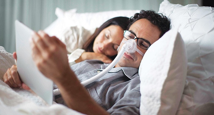 couple in bed cpap machine on